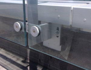 Side mounted rooftop glass railing attachment