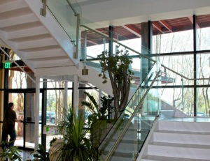 Side mounted glass railing with 36 inch stainless steel handrail on stairs