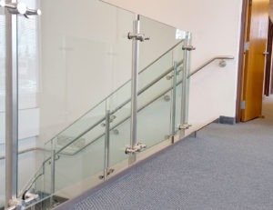 Trapezoidal post supported glass railing on stairs and balcony