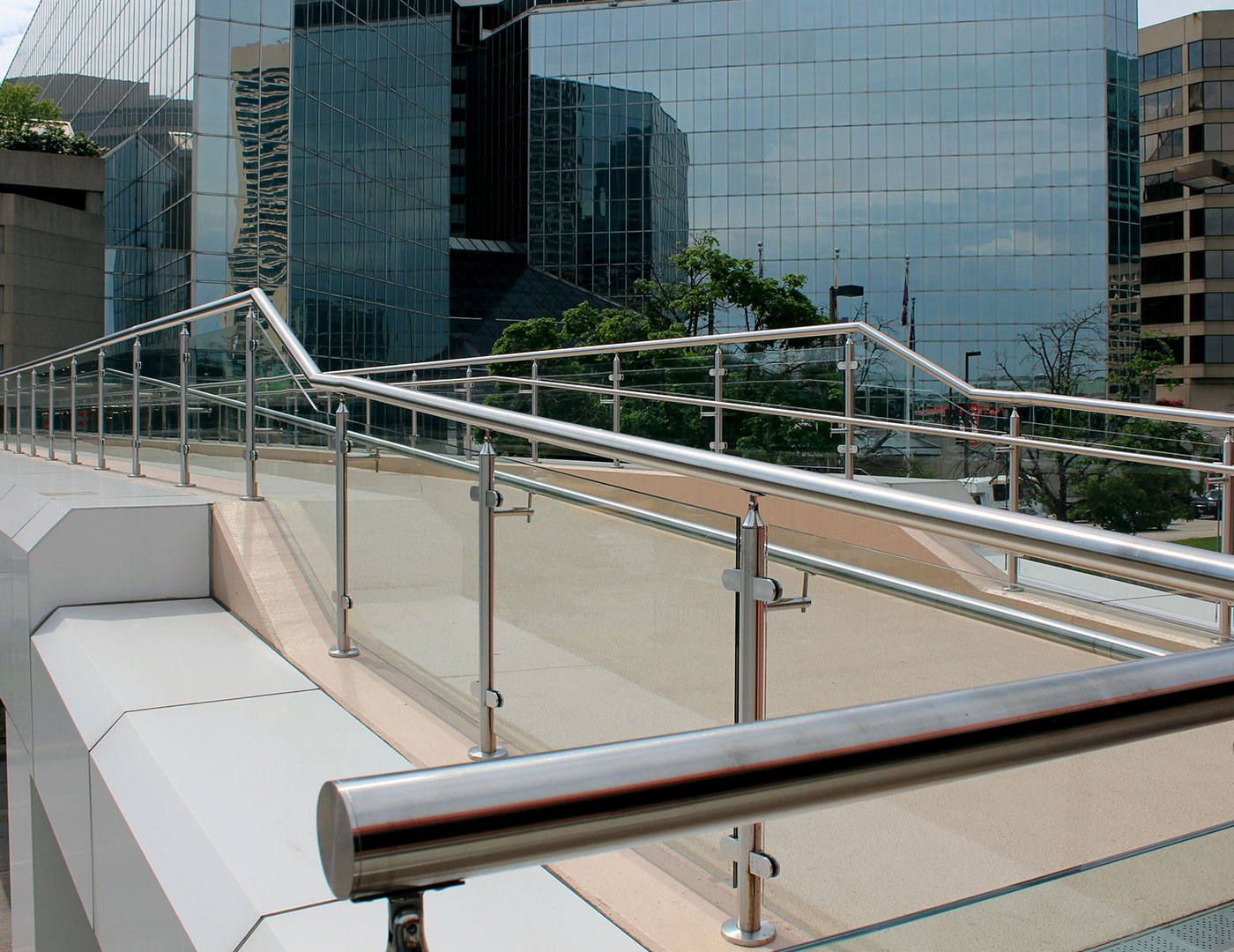 Pedestrian bridge with top mounted glass railing