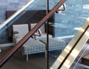 Custom wood handrail attached to glass railing