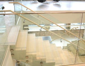 """Base shoe with 1/2"""" glass shoe anchored to the structural slab on balcony overlooks"""