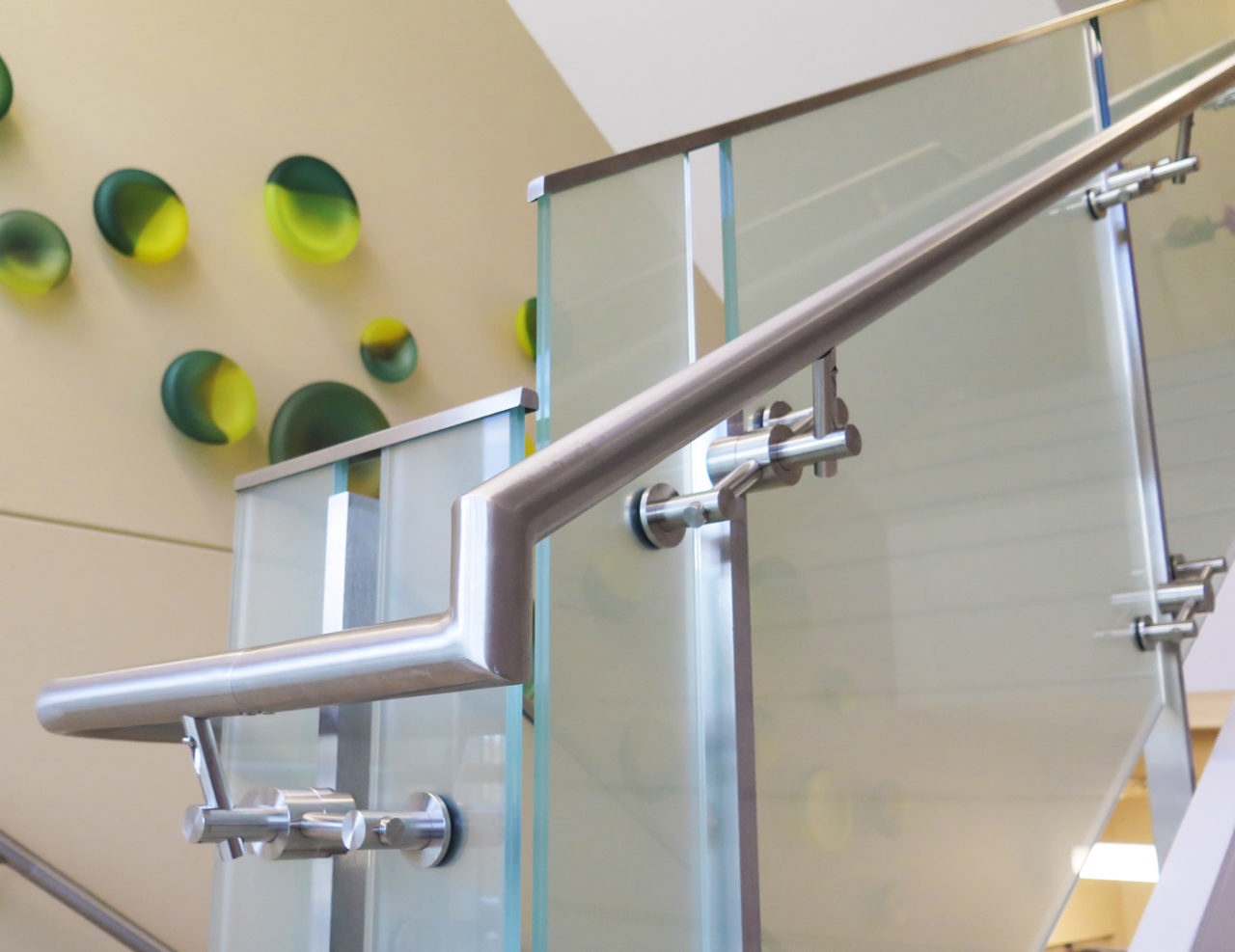 Line series glass railing with stainless steel handrail on stairs and landings in healthcare facility