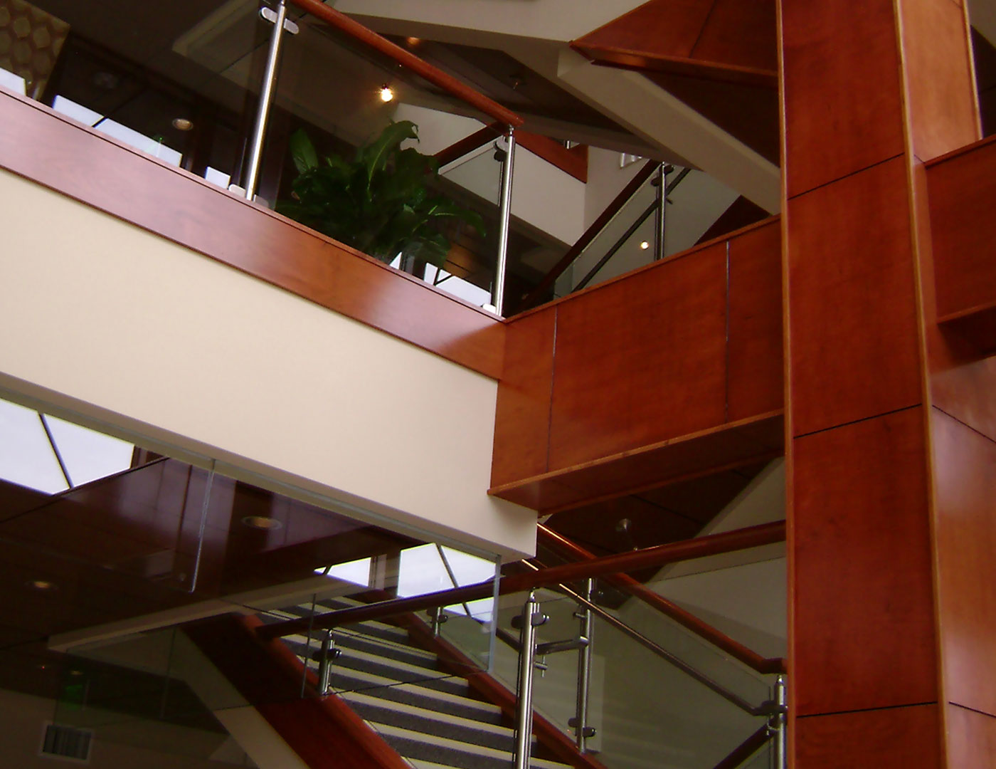 Stainless steel post supported glass railing on interior stairs and balcony overlooks