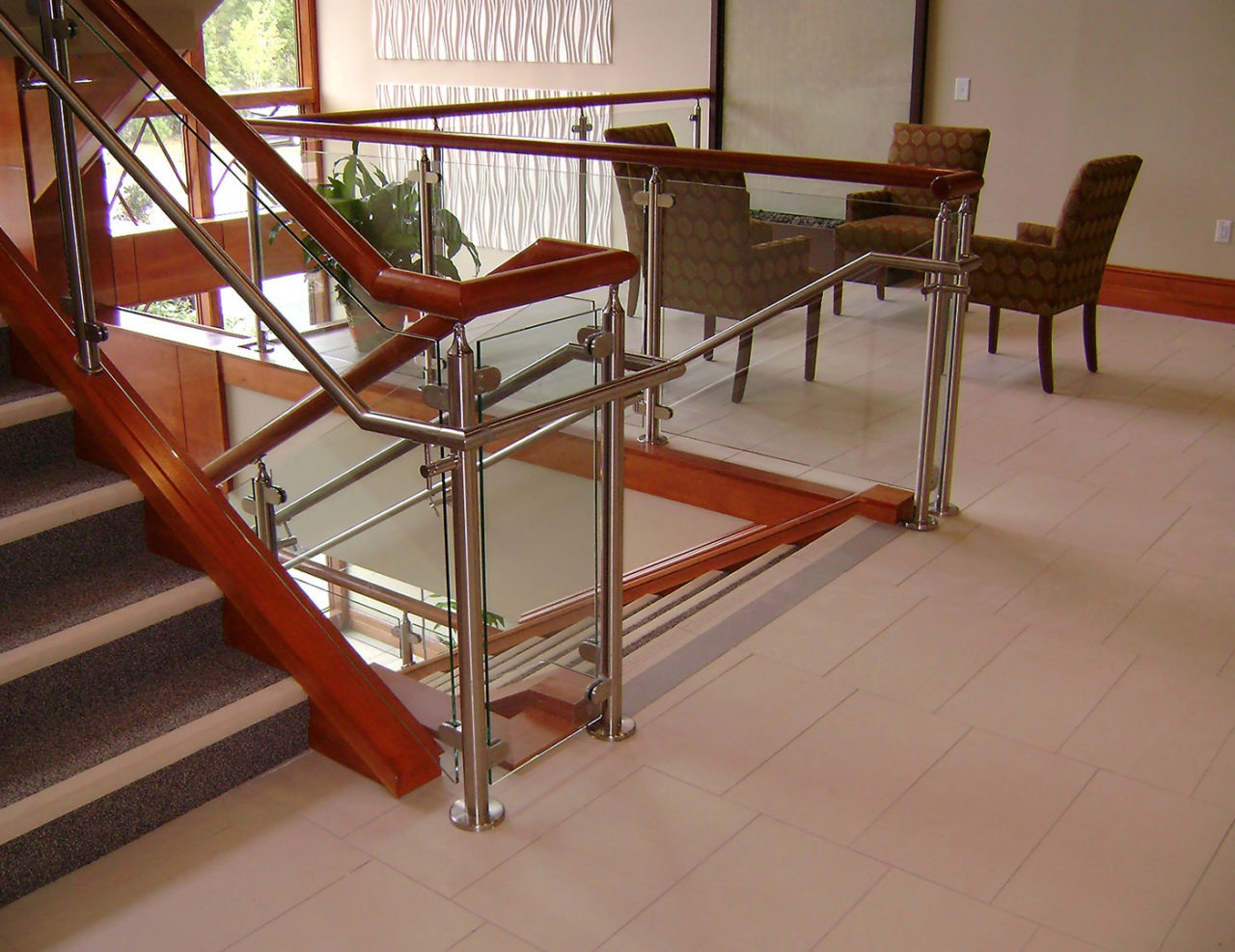 Monaco glass railing with stainless steel handrail and wood top cap