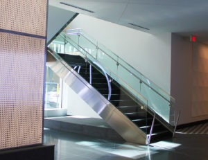 Track Rail glass railing leading to the seating area on the second floor utilizes stainless steel cladding to conceal the stair stringer.