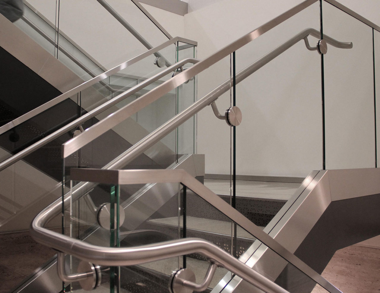 Interior stair and overlook glass railing features stainless steel cladding, top cap, and handrail.
