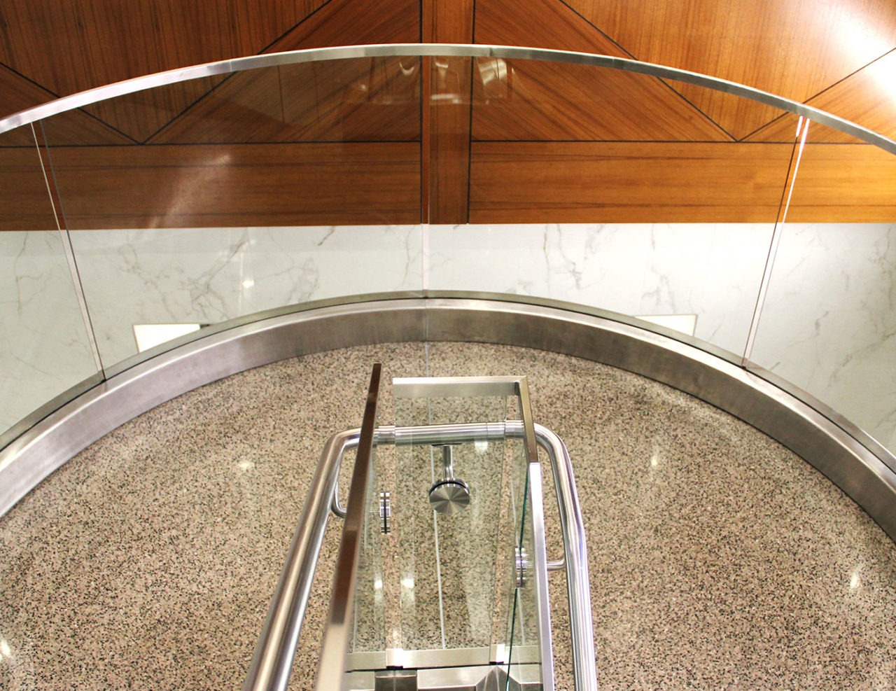 The glass railing on this curved landing required rolled aluminum base shoe, cladding, top cap and glass to achieve the desired tight radius.
