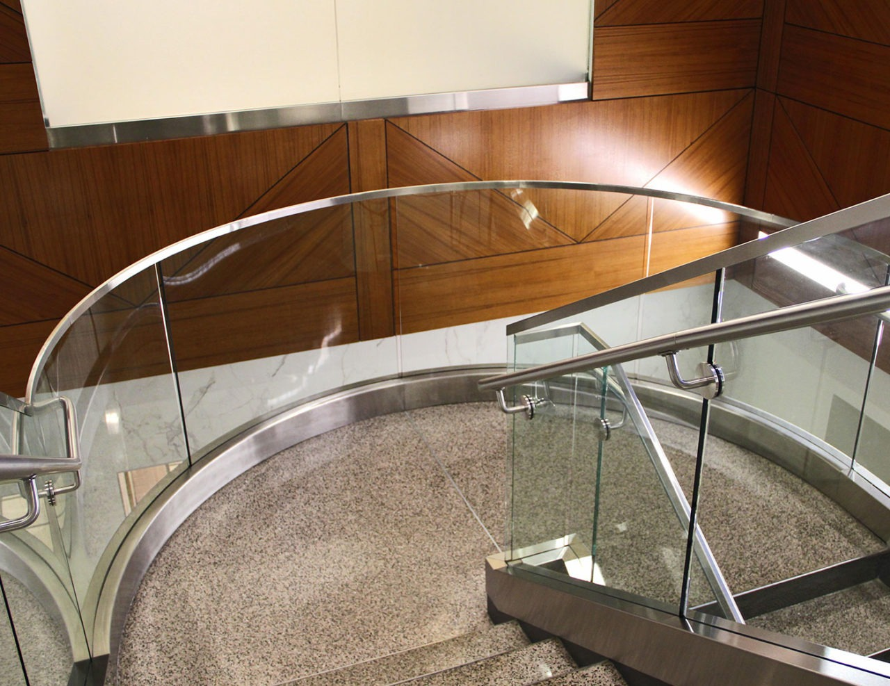 Curved glass railing railing on stair landing achieved by rolling shoe, cladding and top cap.