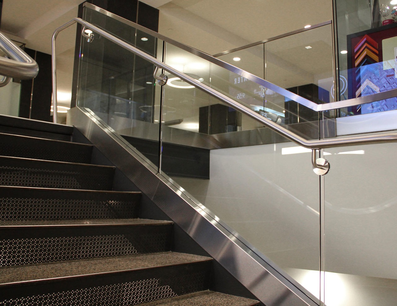 At the top of the stairs, the metal handrail seamlessly transitions from glass infill to floor return.