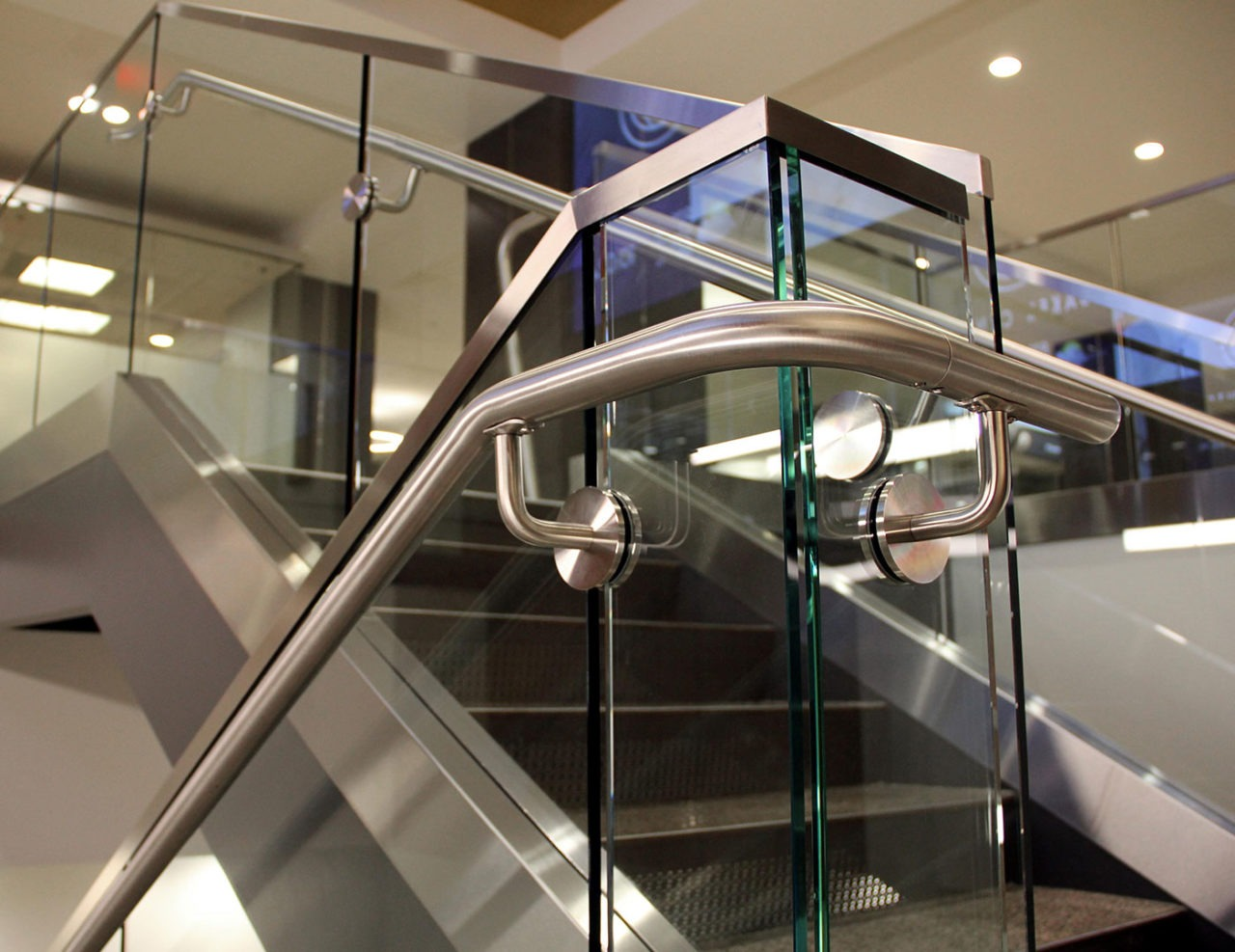 "On interior stairs, stainless steel handrail was attached to 1/2"" clear tempered glass with thru-glass stainless steel standoffs on this glass guardrail system."