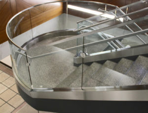 Curved glass railing achieved by rolling shoe, cladding and top cap.
