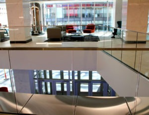 """The newly renovated seating area above the updated main lobby utilized the Track Rail glass railing system with formed top cap and 1/2"""" clear tempered glass."""
