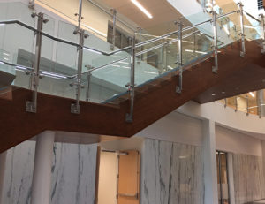 Glass railing posts were welded to mounting plates, which were attached to the stair stringer by drill and tap method.
