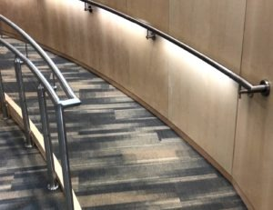 Interior ramp features Casino cable railing with post mounted handrail, and wall mounted LED handrail.