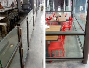 Horizontal aluminum trim pieces feature a bronze anodized finish and are fastened to glass via concealed thru-bolts to complete this glass guardrail