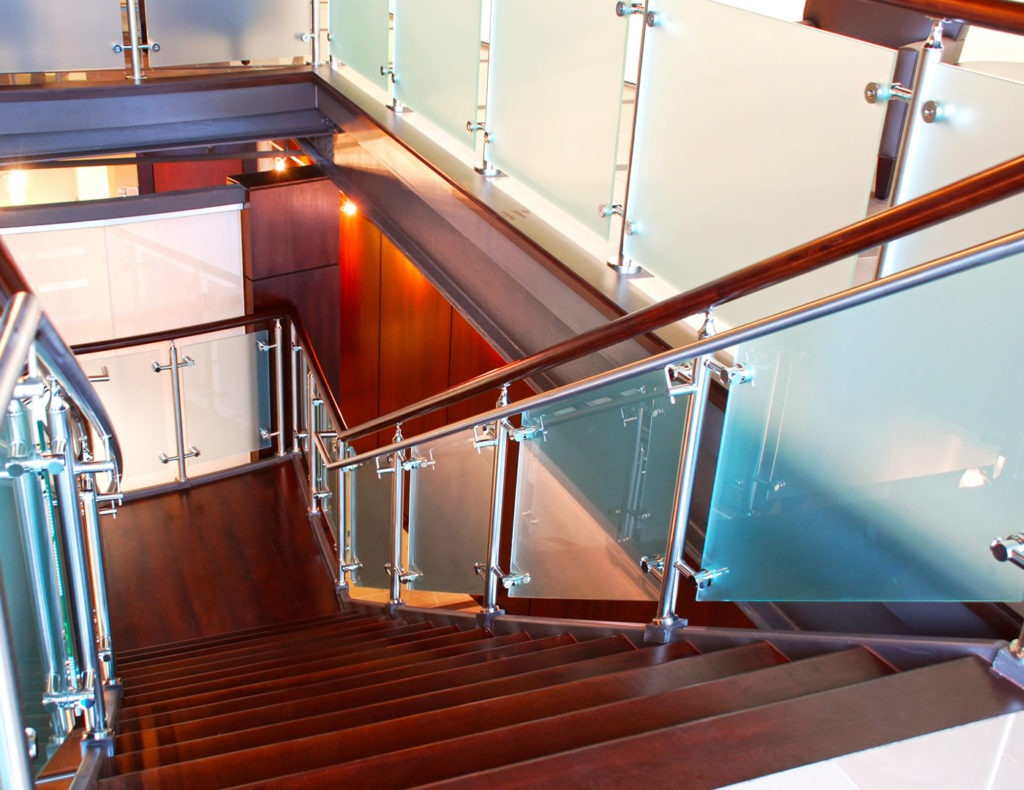 Post mounted glass railing with stainless steel handrails line the stairs, and custom wood top rail found on stairs and landings.