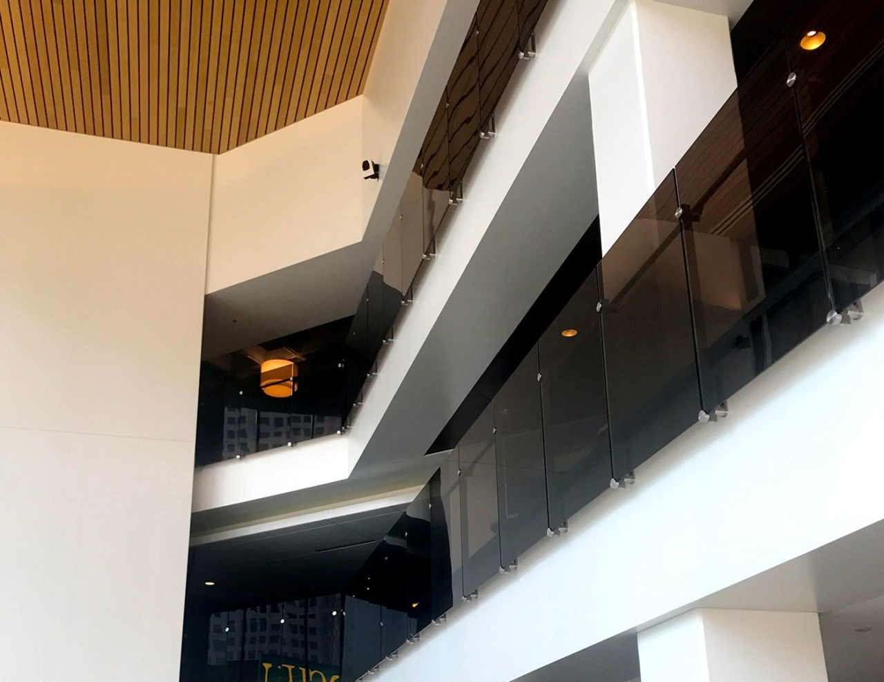 Dot series glass guardrail on multi-level lobby overlooks feature a fascia mount with a stainless steel oval baseplate.
